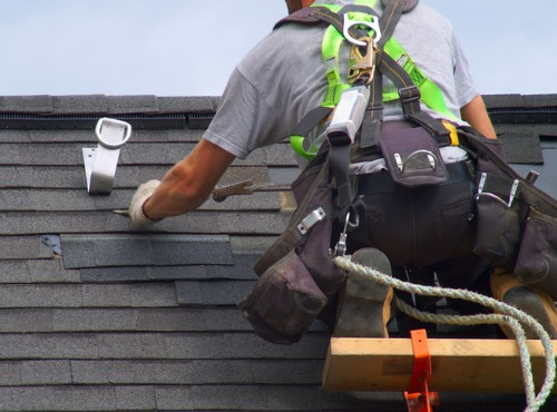 man fixing the shingles on a roof
