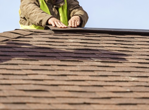 man fixing a roof in Urbana Champaign IL