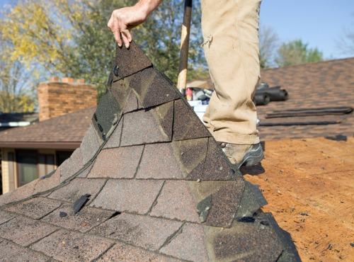 man replacing a roof